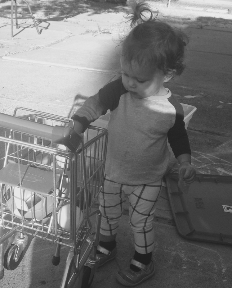 Harlow playing with her own shopping cart in the backyard